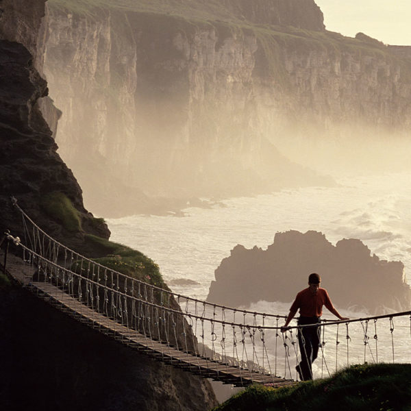 Man Crossing Rope Bridge, Coast of Ireland